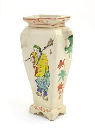 An Oriental vase with twin handles of elephant head form. The body with hand painted figures and