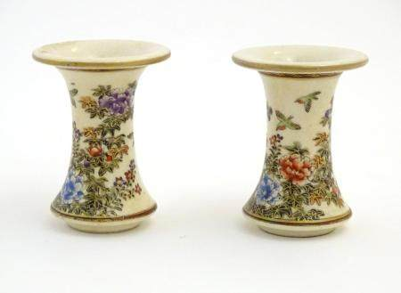 A pair of Japanese miniature Satsuma vases with flared rims and bases, decorated with flowers and