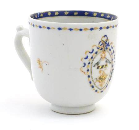 A Chinese export tea cup with hand painted decoration depicting an armorial crest with birds, with a