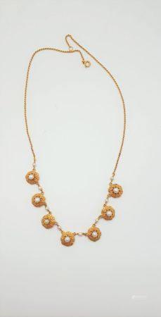 Collier en or jaune 18k (750 millièmes), le décolleté orné de 7 rosaces à motifs de fleurettes