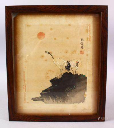 A JAPANESE MEIJI PERIOD WOODBLOCK PICTURE OF TWO CRANES, both cranes stood upon rocky outcrop at sunset, with