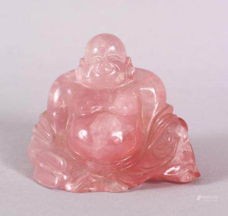 A CHINESE CARVED ROSE QUARTS FIGURE OF BUDDHA, in a reclined position with the usual humorous grin, 6cm high.