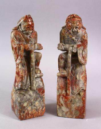 A PAIR OF CHINESE CARVED SOAPSTONE FIGURES OF DEMONS, each demon depicted upon a rocky outcrop with carved clo