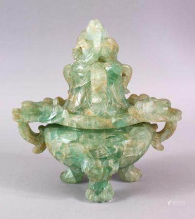 A CHINESE CARVED GREEN QUARTZ TWIN HANDLE VASE AND COVER, with lion dog carved finial's, upon tripod feet, 22