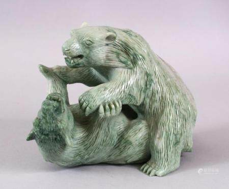 A CHINESE CARVED GREEN HARD STONE MODEL OF TWO PLAYING BEARS, 14cm high x 18cm wide.