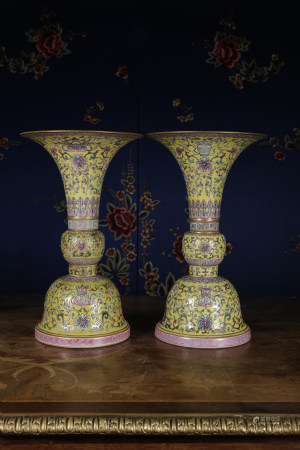 A PAIR OF YELLOW-GROUND FAMILLE ROSE BEAKER VASES.  QIANLONG PERIOD, QING DYNASTY.
