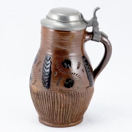 Birnkrug Muskau, um 1879. Beige-graues, salzglasiertes Steinzeug. Schwarz bemalt. Zinnmontier