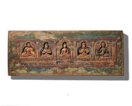 A GILT LACQUERED AND POLYCHROMED WOOD MANUSCRIPT COVER CARVED WITH A KAGYU LAMA, SHADAKSHARI LOKESHVARA, SHAKYAMUNI BUDDHA, PRAJNAPARAMITA, AND GREEN TARA  TIBET, CIRCA 13TH CENTURY