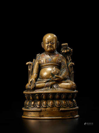 A SILVER AND COPPER INLAID BRASS FIGURE OF LOWO KHENCHEN SONAM LHUNDRUP, ABBOT OF THE KINGDOM OF LO  TIBET, 15TH/16TH CENTURY