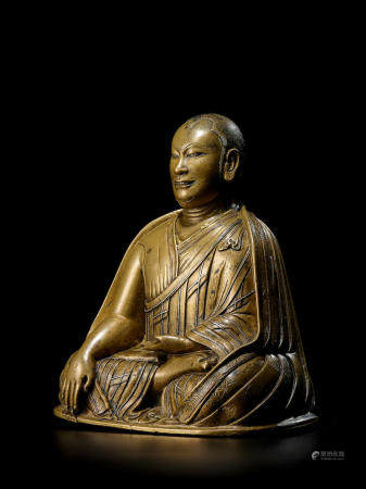 A SILVER AND COPPER INLAID BRASS FIGURE OF A KAGYU LAMA TIBET, CIRCA 13TH CENTURY