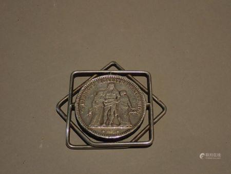 HERMES.  Pince à billets ornée d'une pièce de 5 francs en argent . Dimensions: 5x5,5 cm. Poids: