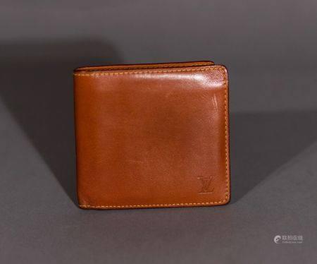 Louis VUITTON. Portefeuille d'homme en cuir nomade.  Deux poches pour billets, trois fentes et