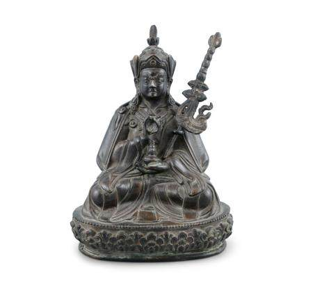 A CHINESE QING DYNASTY BRONZE FIGURE OF A SEATED DEITY, holding a Varja and a ceremonial staff, seat