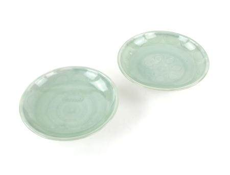 Two Chinese celadon glazed saucer dishes with incised decoration, on round feet, 17.