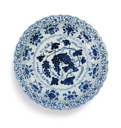 An exceptional and rare blue and white barbed 'grape' charger Ming Dynasty, Yongle Period | 明永樂 青花葡萄紋折沿菱口盤