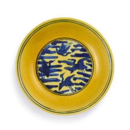 A rare yellow-ground underglaze-blue 'crane' dish Mark and period of Jiajing | 明嘉靖 黃地青花雲鶴紋盤 《大明嘉靖年製》款