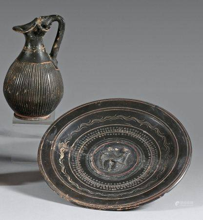 Lot composé de :- Une coupelle à vernis noir ornée au centre d'un tondo en relief avec une Dian