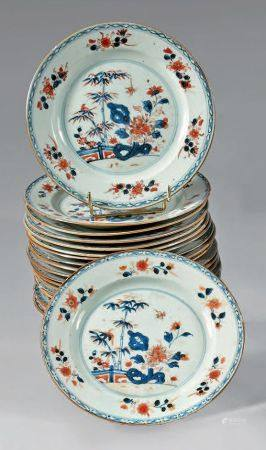 Suite de dix-neuf assiettes en porcelaine décorée en bleu sous couverte, rouge de fer et émail