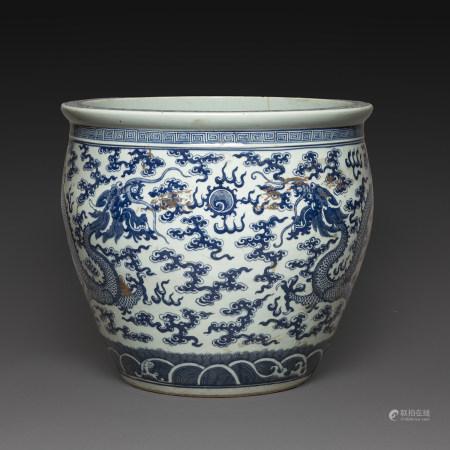 GRANDE VASQUE À POISSONS en porcelaine blanche à décor en bleu sous couverte de dragons affrontés face au joyau sacré parmi des nuages. La base ornée de vagues ondulantes stylisées. Une frise de grec