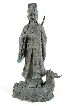 A cast metal sculpture, modelled as the Daoist figure Lu Dongbin standing on a sea monster, with