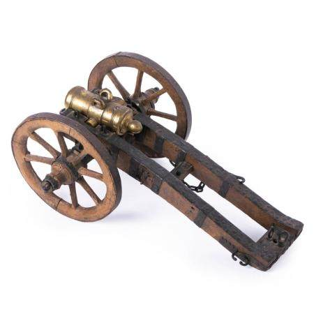 A SHORT COPPER-ALLOY MODEL CANNON MOUNTED ON AN IRON-CLAD WOODEN FIELD CARRIAGE. NOT MARKED. CAL.24M