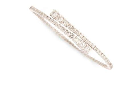 A diamond and fourteen karat white gold bangle bracelet