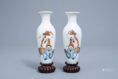 A pair of Chinese polychrome vases with a master and his servant on wooden bases, Wan Yu mark, 20th C.