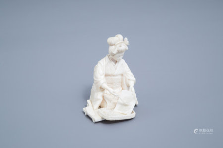 A signed Japanese ivory ikomono of a lady at work, Meiji, 19th/20th C.
