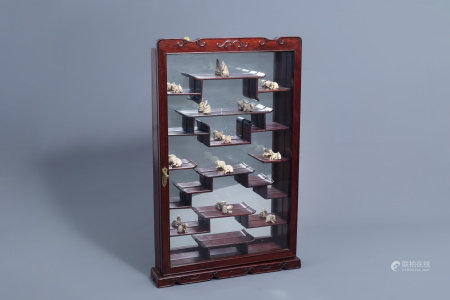 Twelve Japanese ivory animal shaped netsuke in their display cabinet, first half of the 20th C.