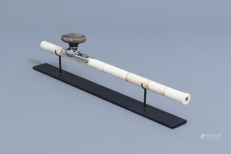 A Chinese ivory opium pipe finished with a silver saddle and a stoneware damper, 19th C.