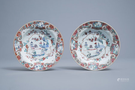 A pair of Chinese deep famille rose plates with figures in a landscape and cranes, Yongzheng/Qianlong