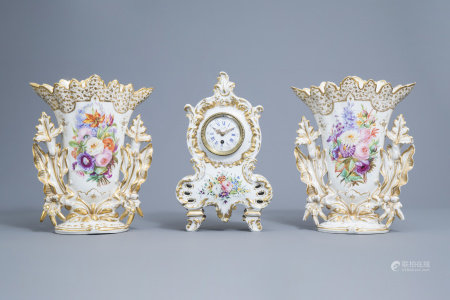 A French mantel clock and a pair of vases in gilt and polychrome old Paris porcelain with floral design, 19th C.