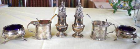 TWO ENGLISH SILVER CRUET SETS comprising of mustard, pepper and salts, some with sapphire blue glass liners. Silver 600 grams. (6)