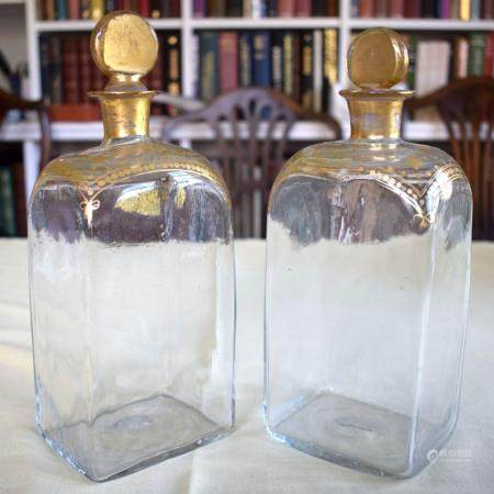 A PAIR OF ANTIQUE BOHEMIAN CLEAR AND GILDED STRAIGHT SIDED GLASS DECANTERS modelled in the neo classical style. 25 cm high.