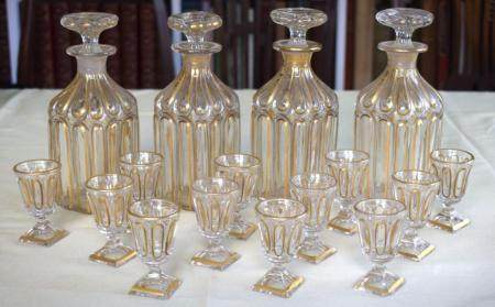 A SET OF FOUR 19TH CENTURY BOHEMIAN CLEAR AND GILDED LIQUOR DECANTERS AND STOPPERS together with matching smaller glasses. Decanters 19 cm high. (15)