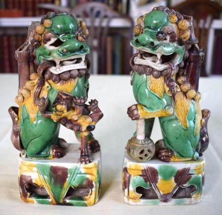 A PAIR OF 17TH CENTURY CHINESE EGG AND SPINACH GLAZED BUDDHISTIC LIONS modelled upon similarly decorated openwork bases. 21 cm x 7 cm.