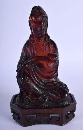 AN EARLY 20TH CENTURY CHINESE CARVED AMBER TYPE FIGURE OF GUANYIN late Qing/Republic, upon a fitted hardwood stand. 301 grams. Figure 14 cm x 6 cm.
