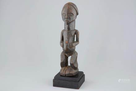 An African carved wood fetish figure on stand, Songye, Congo, mid 20th C.