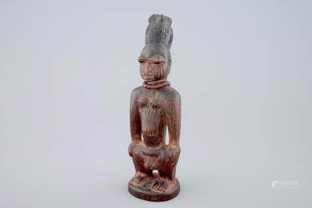 An African carved wood figure, Yoruba, Nigeria, 2nd/3rd quarter of the 20th C.