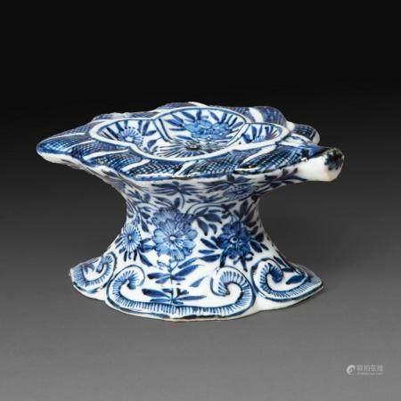 SALERON en porcelaine bleu-blanc, en forme de feuille montée sur piédouche, à décor de tiges florales, le pied bordé de quatr...