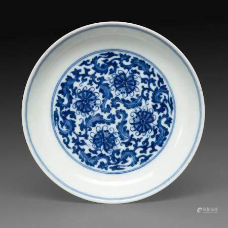 COUPE en porcelaine blanche à décor en bleu sous couverte de fleurs de chrysanthème et rinceaux feuillagés en médaillon central...