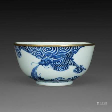 """COUPE en porcelaine bleu-blanc dite """"de Hué"""", à décor d'un dragon parmi les nuées, la base animée de poissons émergeant de vagu..."""