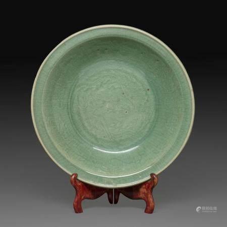 GRAND PLAT CREUX en porcelaine et émail céladon craquelé, à décor incisé sous la couverte, de deux phénix en médaillon central,...