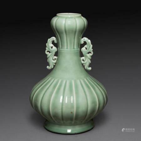 VASE reprenant la forme d'une coloquinte, orné de deux anses feuillagées, en porcelaine et émail céladon, la panse et le col go...
