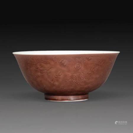 COUPE en porcelaine et émail manganèse à décor sous couverte de dragons pourchassant la perle sacrée parmi les nuées. Marque e...