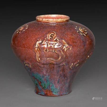 VASE PANSU en céramique, émaux flammés sang-de-bœuf et violet-vert sur fond brun, à décor moulé sous la couverte de trois drago...