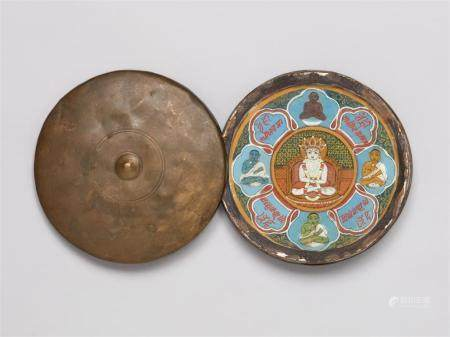 A portable Jain Shvetambara Siddhachakra. Pigments on paper, glass and a copper alloy container. Western India. 19th/20th century