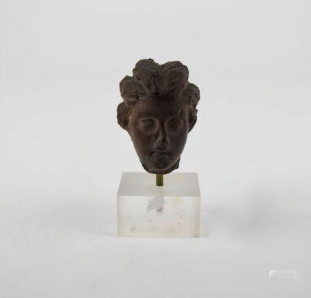 Tête féminine en terre cuite de style grécoromain. H : 4,5cm