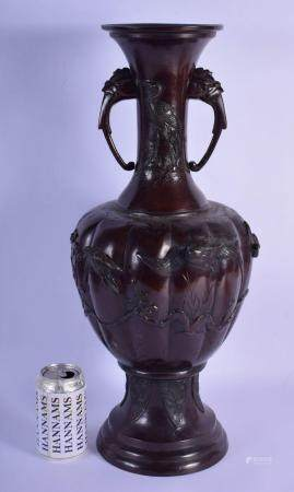 A LARGE 19TH CENTURY JAPANESE MEIJI PERIOD TWIN HANDLED BRONZE VASE decorated with foliage and vines. 53 cm x 18 cm.