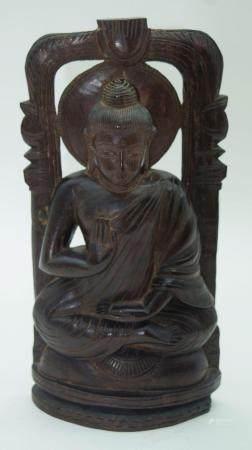 A carved hardwood South East Asian seated Buddha on a shrine. 30cm.